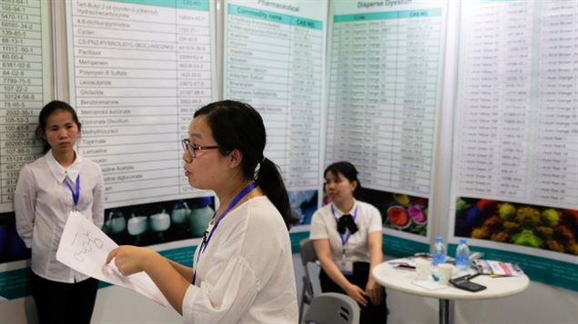Xu Liqun, centre, president of Hangzhou Reward Technology, speaks at the company's booth during the China International Chemical Industry Fair in Shanghai on Sept. 21. Liqun said her company could produce carfentanil to order. (Andy Wong/The Associated Press