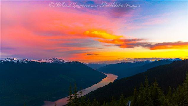 Une rivière sépare des montagnes de forêts canadiennes, le tout sous un ciel orangé.