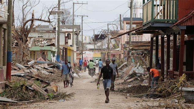 Un homme marche dans une rue dévastée de Port-à-Piment, en Haïti, en octobre 2016