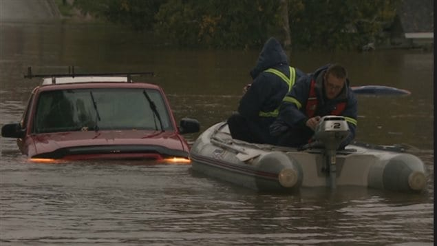 emergency crew comes to the aid of  people in a vehicle caught in the sudden flood in Sydney, N.S