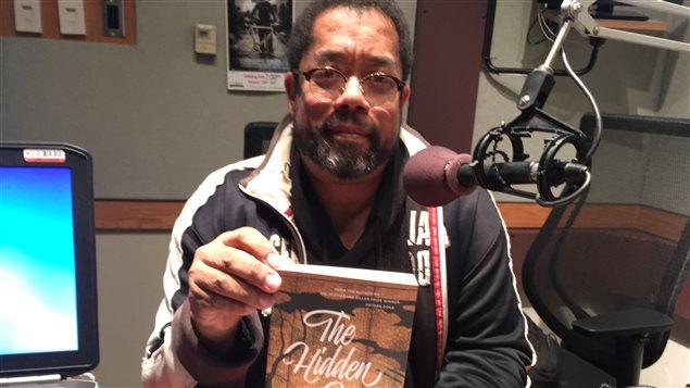 Un homme dans un studio de radio tient un livre