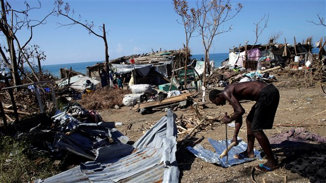 A man cuts a metal sheet using a machete and a stick after Hurricane Matthew in Les Anglais, Haiti, October 13, 2016.