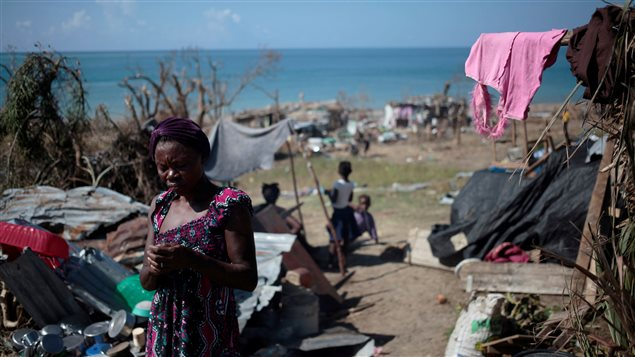 A woman stands by her house as she cooks after Hurricane Matthew in Les Anglais, Haiti, October 13, 2016.