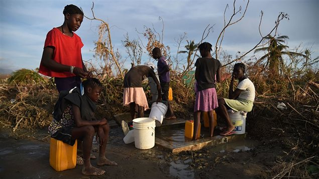 Haitians pump water from a cistern next to the road, in the commune of Chadonyer, in Les Cayes, in the south west of Haiti, October 11, 2016.