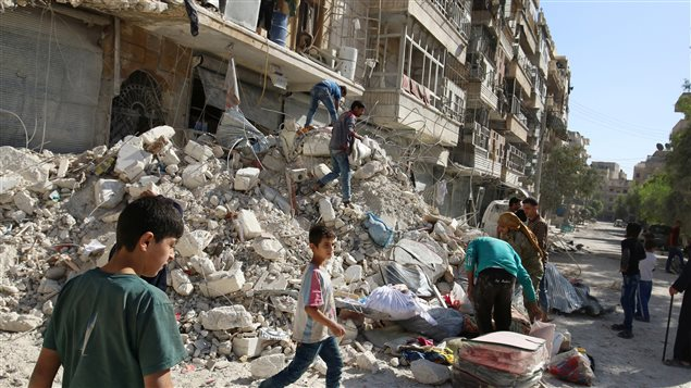 People remove belongings from a damaged site after an air strike Sunday in the rebel-held besieged al-Qaterji neighbourhood of Aleppo, Syria October 17, 2016.