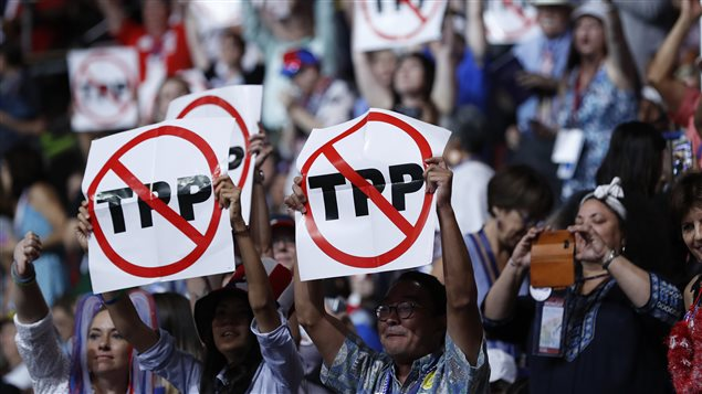 Delegates protesting against the Trans Pacific Partnership (TPP) trade agreement hold up signs during the first sesssion of the Democratic National Convention in Philadelphia, Pennsylvania, U.S. July 25, 2016.
