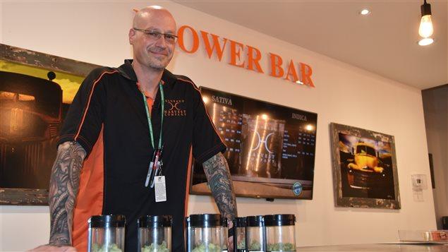 Un homme avec des pots contenant de la marijuana devant lui