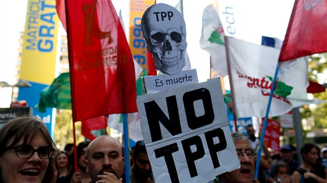 Activists shout slogans during a protest against the TPP (Trans-Pacific Partnership) and Monsanto Co, the world's largest seed company at Santiago, Chile, January 22, 2016.
