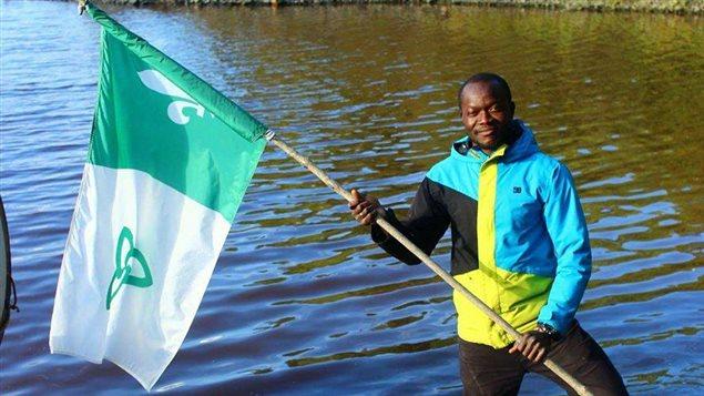 Elvice Aguida tient un drapeau franco-ontarien.