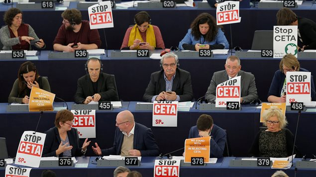 Members of the Confederal Group of the European United Left of the European Parliament display posters with the words *stop CETA* as they take part in a voting session at the European Parliament in Strasbourg, France, October 26, 2016.