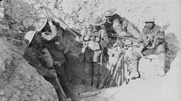 Mud-splattered Canadians take a pause in a former German trench on Hill 70.