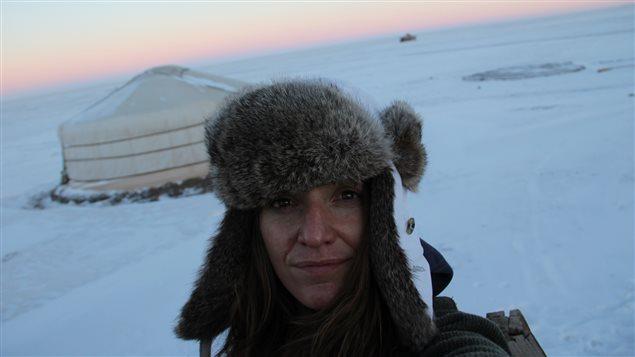 Une femme avec un chapeau de poil sur la tête dans la neige