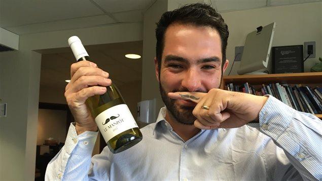 Un homme avec une bouteille de vin et une moustache peinturée sur le doigt, placé au-dessus de sa bouche.