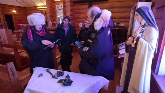 L'historienne Juliette Champagne fait la lecture des documents de Mgr Grandin et du père Le Chevallier devant les restes de la cloche de Batoche, dans l'église de Saint-Laurent de Grandin.