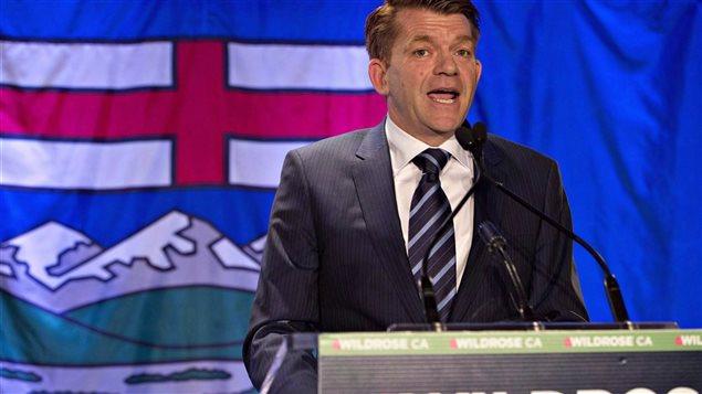 Le chef du parti d'opposition officielle Wildrose Brian Jean, devant un drapeau albertain.
