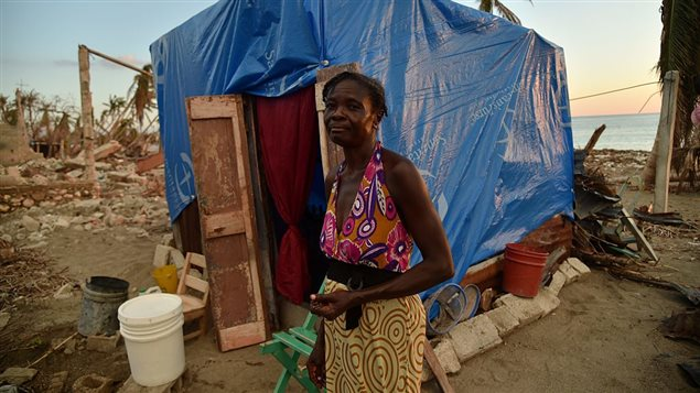Anne Marie looks on next to her shelter, built with metal, wood and plastic tarpaulin, in the place where was her house was destroyed by hurricane Matthew, in the commune of Coteaux, southwestern Haiti, on November 4, 2016.