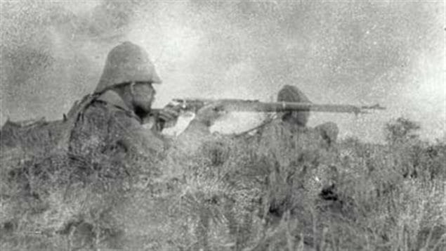 "Canadians firing at the Boer trenches between 50 and 200 metres away. Possibly the first photo taken of a front line battle. Photo by J Cooper Mason, who later wrote to his family ""The fire at this point was very hot,"" As he took this photo a Boer bullet hit his helmet, taking the maple leaf badge off the front. He fortunately was unhurt."