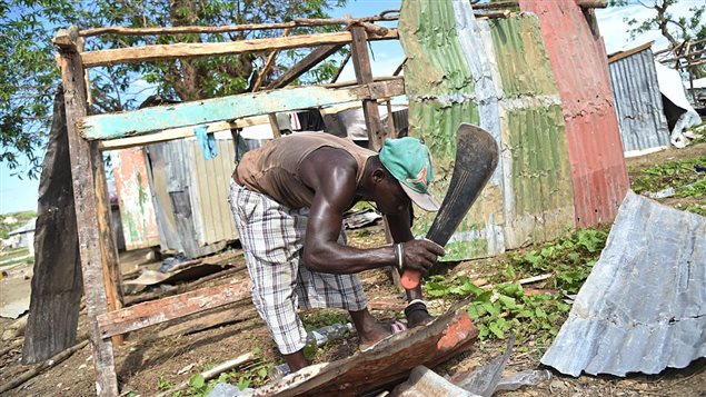 Venel Lague builds his shelter at a informal camp for people who lost their houses during the passage of the Hurricane Matthew, in the neighborhood of Gebeaux, in the commune of Jeremie, southwestern Haiti, on November 5, 2016.