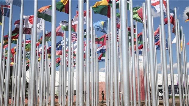 Un agent de sécurité parmi des dizaines de drapeaux hissés sur le site de la Conférence onusienne sur le climat à Marrakech au Maroc
