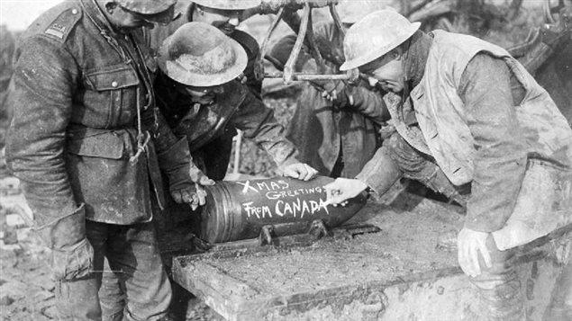 Des soldats de l'artillerie canadienne ajoutent un message à leur projectile Photo : Collection d'archives de l'Imperial War Museum