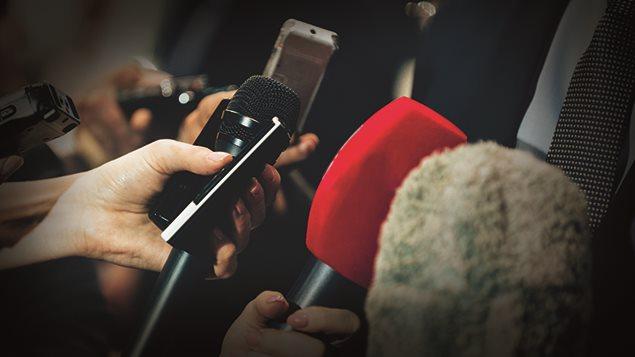 Des mains et des micros des journalistes