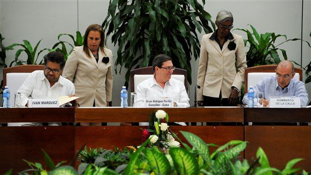 El jefe de la delegación de las FARC Iván Márquez (izq) y el jefe negociador del gobierno colombian Humberto de la Calle (der) firman el nuevo acuerdo de paz en presencia del ministro de Relaciones Exteriores de Cuba, Bruno Rodríguez Parrilla (centro) en La Habana, Cuba, este sábado 12 de noviembre 2016.