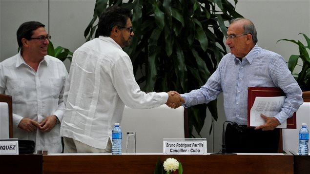 Iván Márquez y Humberto de la Calle, se dan un apretón de mano después de la firma del nuevo acuerdo de paz.