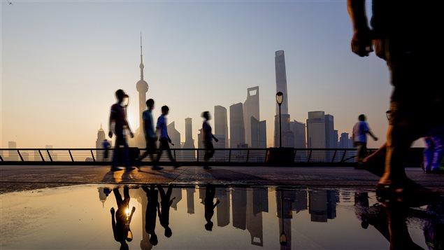 Des passants devant la ville de Shanghai au loin