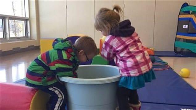 Deux enfants jouent avec un grand bac dans une garderie