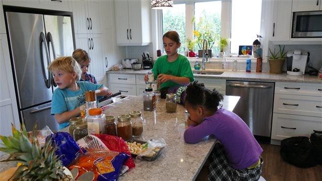 Quatre enfants autour d'un ilôt de cuisine