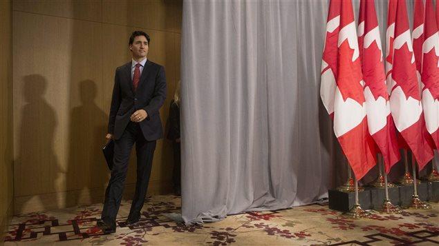 Justin Trudeau entre dans une salle où se trouve plusieurs drapeaux canadiens.