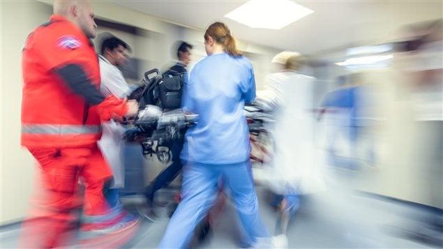 Une équipe transportent un patient sur une civière à l'urgence
