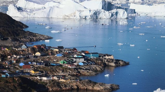 The village of Ilulissat next to arctic waters and an iceberg.