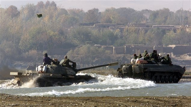 Northern Alliance troops riding on a BMP-1  infantry fighting vehicle (R) and a T-55 tank (L) cross a river in northeastern Afghanistan not far from where a three western journalists were killed in a Taliban ambush on Nov. 11, 2001.