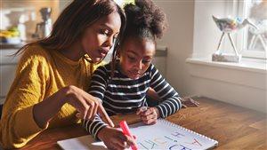 Une maman supervise sa fille qui fait ses devoirs