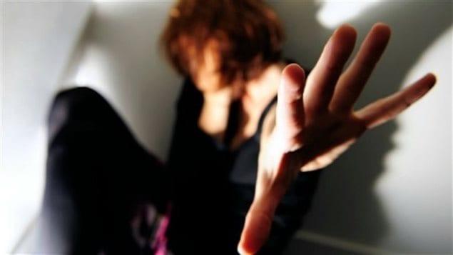 Une femme tend la main devant elle pour se protéger