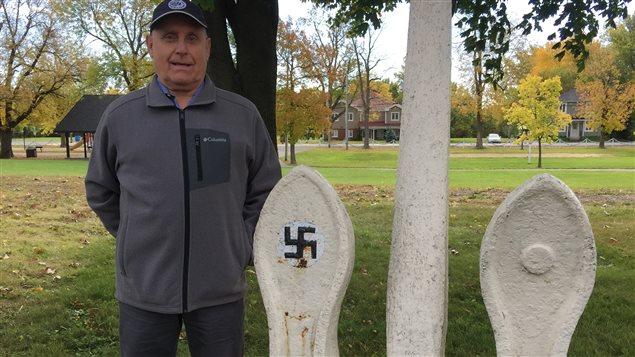 Raymond Poirier, amateur d'histoire et citoyen de Pointe-des-Cascades, à côté de l'ancre qui arbore la croix gammée