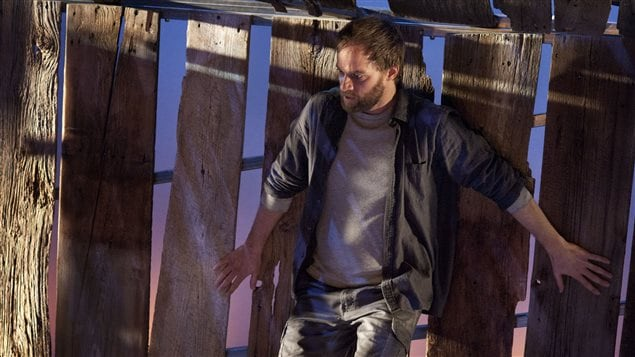 Le comédien David Boutin, debout le long d'une clôture en bois.