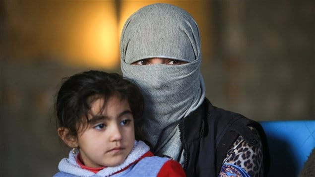 A displaced woman from the minority Yazidi sect, who was kidnapped by Islamic State militants of Tal Afar but managed to flee, holds a child in Duhok province, northern Iraq, November 24, 2016.