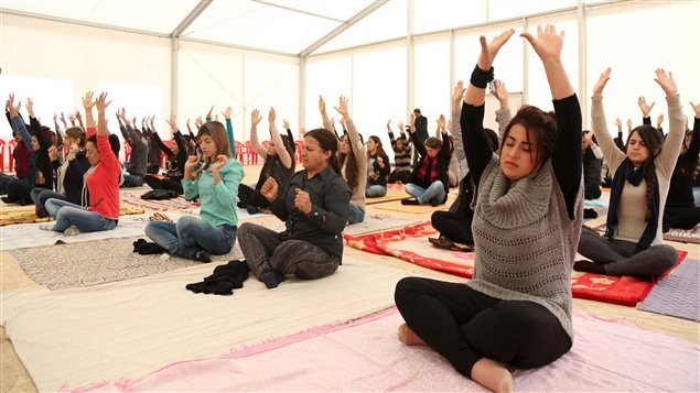 Displaced women from the minority Yazidi sect, who fled violence in the Iraqi town of Sinjar, practice yoga at Sharya refugee camp on the outskirts of Duhok province, December 16, 2015.