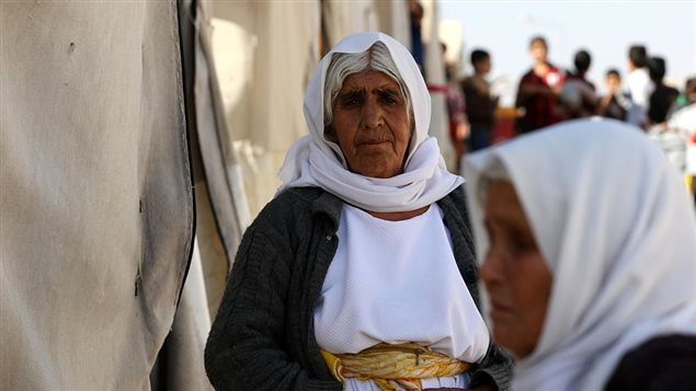 A displaced Iraqi woman from the Yazidi community, who fled violence between Islamic State (IS) group jihadists and Peshmerga fighters in the northern town of Sinjar, stands at a camp for internally displaced persons (IDP) in the Sharia area, some 15 kilometres from the city of Dohuk, on November 17, 2016.