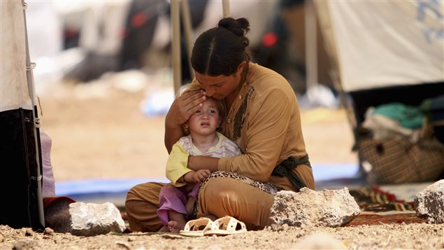 A refugee woman from the minority Yazidi sect, who fled the violence in the Iraqi town of Sinjar, sits with a child inside a tent at Nowruz refugee camp in Qamishli, northeastern Syria August 17, 2014.
