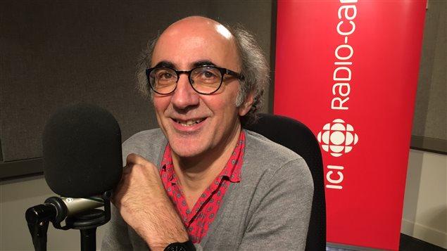 L'auteur Dominique Fabre pose derrière un microphone.