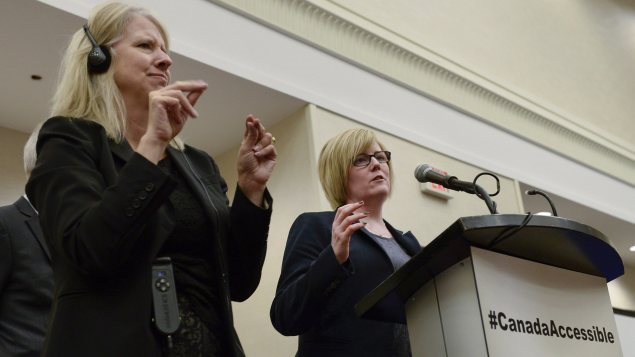 La ministra Carla Qualtrough (derecha) acompañada de una intérprete que traduce sus declaraciones en lengua de signos.