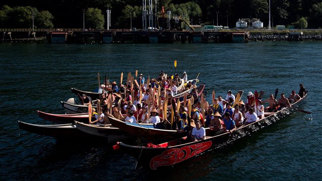 Members of the Squamish and Tsleil-Waututh First Nations gather in canoes on the waters of Burrard Inlet at the Kinder Morgan Burnaby Terminal for a ceremony to show opposition to the expansion of the Trans Mountain pipeline, in North Vancouver, B.C., on Saturday September 1, 2012.