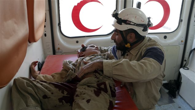 A civil defence member holds an injured boy inside an ambulance after what activists were were cluster bombs dropped by Russian air force in Maaret al-Naaman town in Idlib province, Syria October 7, 2015.