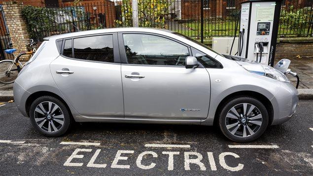 Auto eléctrico conectado a su fuente de energía