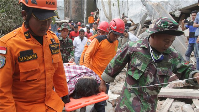 Indonesian rescue workers carry a survivor from a fallen building after an earthquake in Ulee Glee, Pidie Jaya, in the northern province of Aceh, Indonesia December 7, 2016.