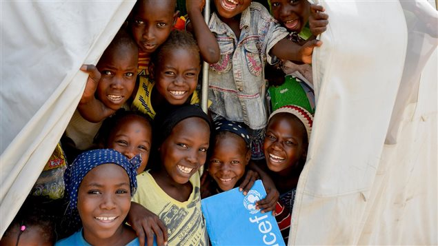 Nigerian Children Stand In A Tent Provided By Unicef Holding Exercise Books From The Charitys School