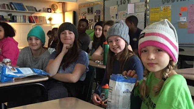 Des élèves de l'École Précieux-Sang portent leurs tuques en visionnant le film La Guerre des tuques.